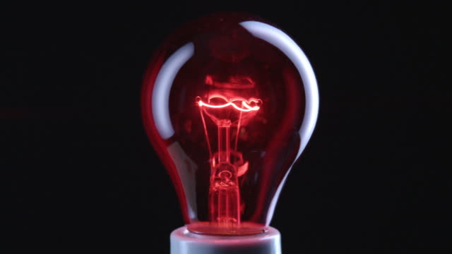CU Studio shot of red incandescent light bulb