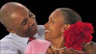 CU, Studio shot of senior man giving red roses to woman