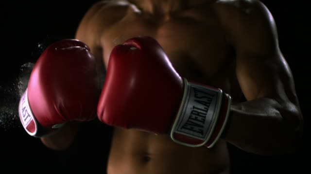 SLO MO CU Studio shot of shirtless man wearing boxing gloves, mid section