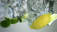 SLO MO CU Studio shot of slices of limes and lemon falling into water