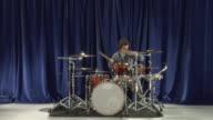 WS ZI MS Studio shot of teenage boy (16-17) playing drums