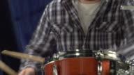 MS CU Studio shot of teenage boy (16-17) playing drums