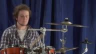 CU ZI Studio shot of teenage boy (16-17) playing drums