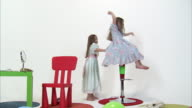WS Studio shot of twin sisters (8-9) dressed for party playing on tall chair / Orem, Utah, USA