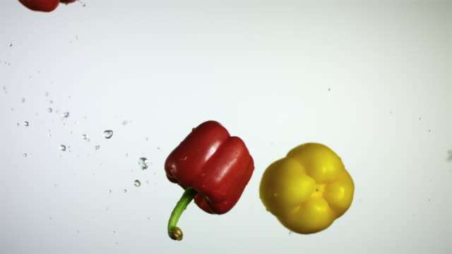 SLO MO CU Studio shot of water splashing on yellow and red bell peppers
