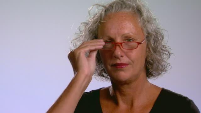 Studio shot of woman putting on reading glasses
