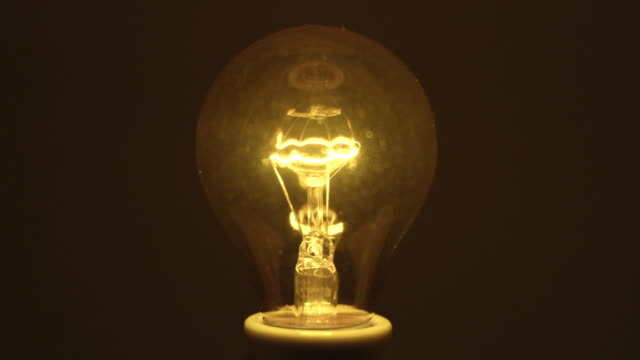 CU Studio shot of yellow incandescent light bulb