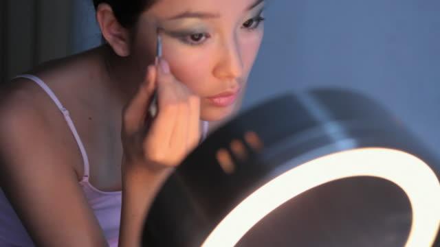 CU SHAKY HA R/F ZI ZO PAN Studio shot of young woman applying eye shadow in front of mirror