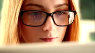 Studying online, young woman wearing glasses.