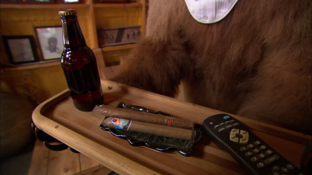 A stuffed bear holds a tray of beer, cigars and a remote control in the lobby of a ski lodge.