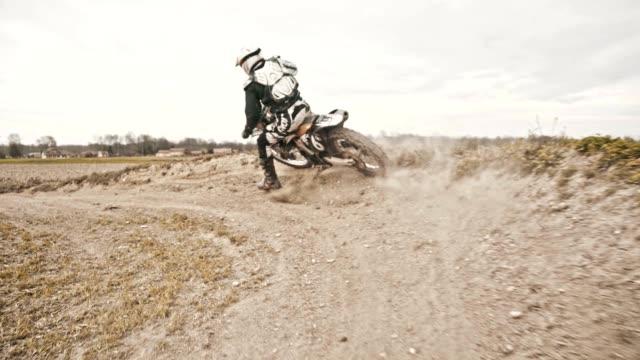SLO MO Stunt dirt biker drifting through the turn