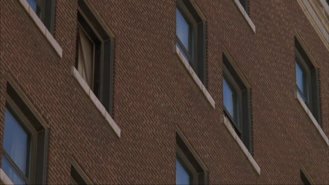 A stunt man jumps out the top story window of a brick building.