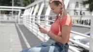 Stylish female in headphones surfing in smartphone