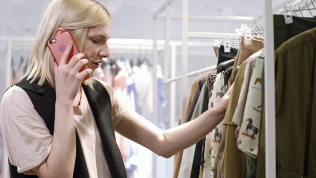 Stylish transgender person chatting on mobile phone while shopping
