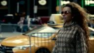 Stylish woman in sunglasses walking along New York street
