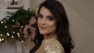 Stylish woman smiling and posing in a sparkly dress at a holiday party