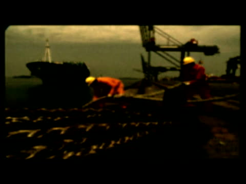 Stylized scenes of dock-workers on dockside pulling ropes