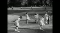 Suburb street w/ cars parked in front of houses children playing in open field girls jumping rope playing hopscotch while boys play baseball /...