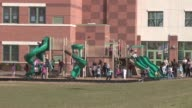 Suburban Elementary School / Exterior of Elementary School / Children playing on a jungle gym in front of school Suburban Elementary School at Cherry...