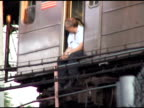 Subway driver sitting in open doorway of stalled subway car on the Queensboro Bridge as he looks down on the crowds walking across the bridge 2003...
