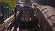 Subway train passes by the 1 train sitting stationary on tracks in Harlem, New York City.
