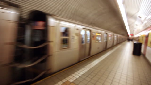 Subway train passes through station as street musician plays acoustic guitar on platform