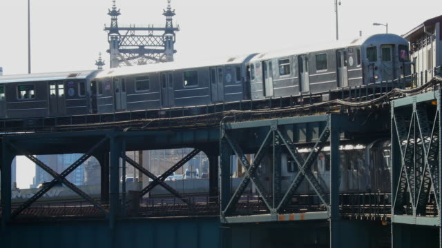 Subways run on elevated railroad at Queens New York. Cars run under the railroad.