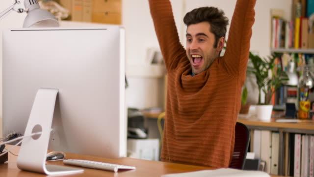Successful creative businessman celebrating the productive day