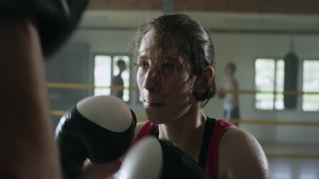 Successful female boxer hitting boxing mitts at gym