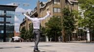SLO MO Successful yuppie showing joy on a skateboard