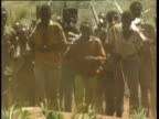 Sudan Peoples' Liberation Army soldiers some with weapons dancing and marching on dusty ground