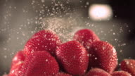 sugar drizzling over strawberries