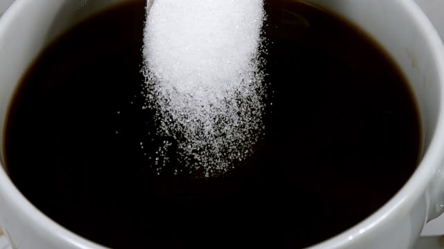 CU SLO MO Sugar falling into bowl of coffee / Vieux Pont, Normandy, France
