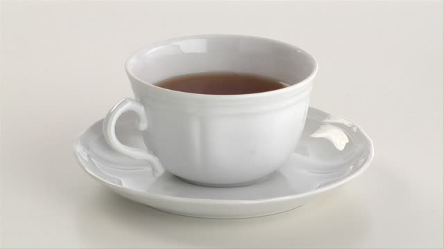 CU, Sugar falling into cup of tea