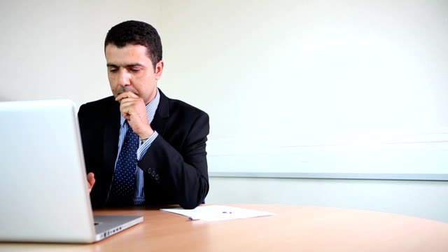 Suited male lawyer working on laptop