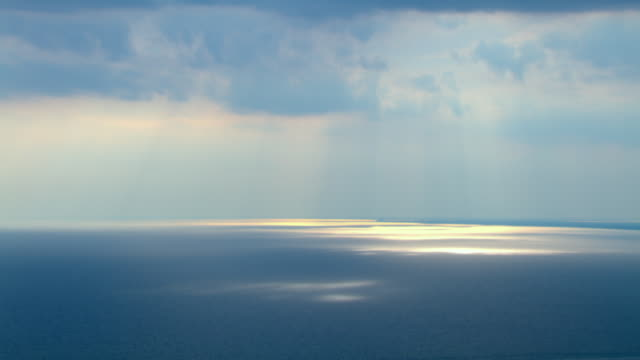 Sun beams downward through wispy clouds over the calm waters of the Gulf of Mexico.