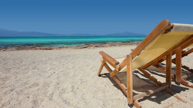 HD: Sun chairs on sandy beach