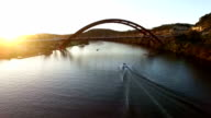 Sun Flares Boats Fun Times on The Water Pennybacker Bridge or 360 Bridge or Capital of Texas Highway Bridge at Sunset on the Colorado River or Town Lake Spring Time Aerial Following a Boat on the water speeding into the Sunlight
