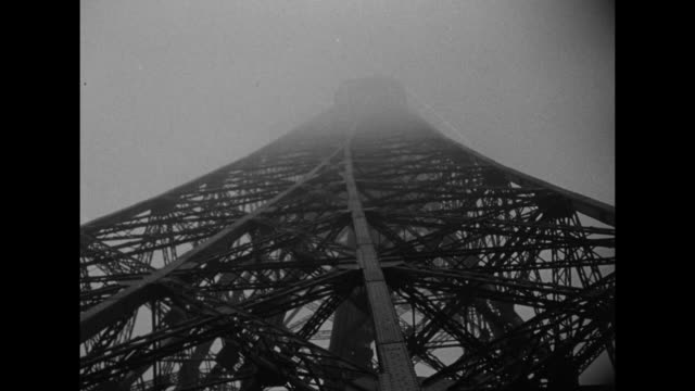 WS sun peeks through fog behind the Eiffel Tower / tiltup shot from base of Tower of intricate frameworks fog shrouds the top of the Tower / man...