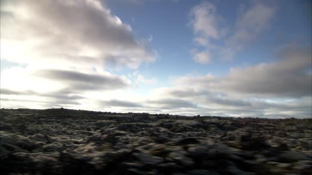 Sun penetrates clouds and shines down on a gray plain covered in volcanic rock. Available in HD