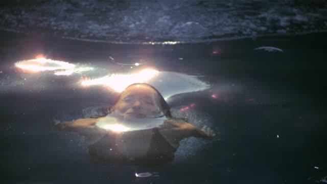 SLO MO MS Sun reflecting on woman surfacing from water/ California, USA