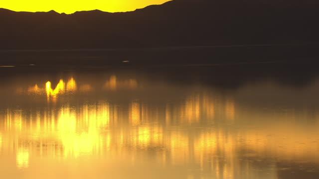 CU AERIAL TU Sun reflection in great salt lake and blazing orange sunset behind mountain / Utah, United States