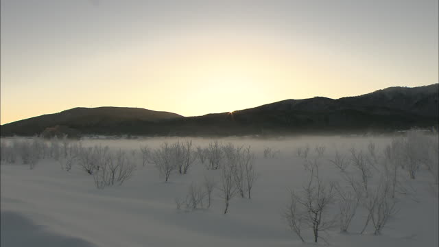 Sun rises over silhouetted mountains, snowy plain in foreground