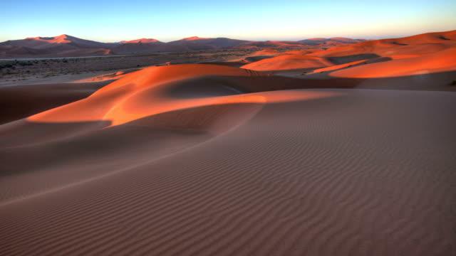 Sun rising on rippled sand dunes of Sossusvlei