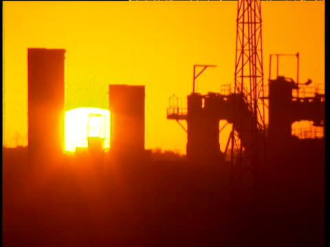 Sun sets behind power station silhouetted against orange sky Democratic Republic of Congo