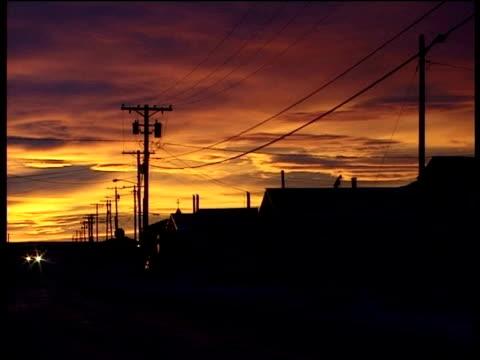 Sun sets over snow covered street in town of Kotzebue Alaska