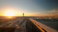 WS T/L Sun setting behind airport runways at Phoenix Skyharbor Airport with control tower / Phoenik, Arizona, USA