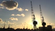Sun setting behind cranes at Royal Victoria Dock in east London England Sunset at Royal Victoria Docks at Royal Victoria Docks on November 04 2013 in...