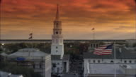 ZI Sun setting beyond American flags raised on poles and St Michael's steeple / Charleston, South Carolina, United States