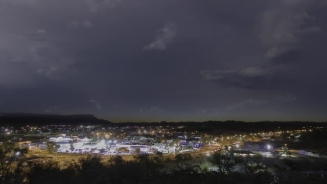 T/L WS ZI Sun setting over outback town, as night falling thunderstorm with lightning flashing / Alice Springs, Northern Territory, Australia